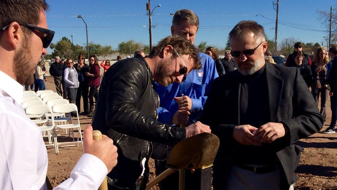 Country star Dierks Bentley signs a shovel used to break ground on his latest Whiskey Row restaurant and bar in downtown Gilbert on Feb. 2.
