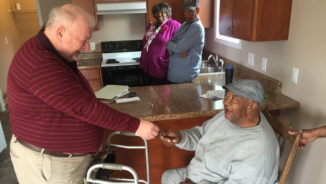 Murfreesboro's Community Development Director John Callow, left, hands keys to new homeowner Felix Johnson, whose home was constructed through a grant facilitated by the city.