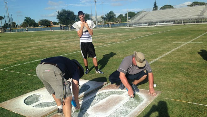 Eau Gallie football coach Tim Powers (in hat) helped paint field numbers last week in an attempt to move Friday's game to Wednesday.