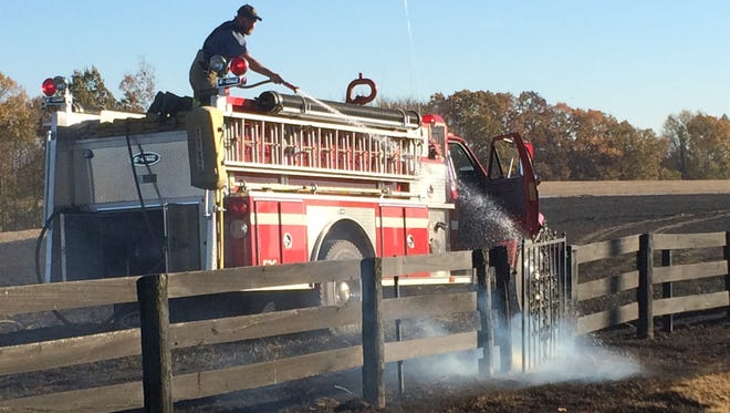 A firefighter works to extinguish part of a burning fence as crews work to contain a wildfire in Robertson County on Friday, Nov. 18, 2016.