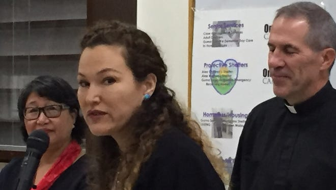 Ramona Jones, vice chair of Catholic Social Service's board of trustees, speaks at a press conference Tuesday morning, while Archbishop Michael Jude Byrnes, right, and Catholic Social Services executive director Diana Calvo, left, look on.