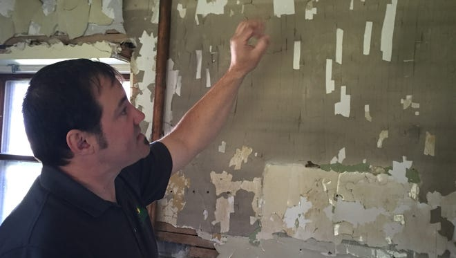 Dennis Delor shows where a kitchen cabinet once was in the Lightkeepers Duplex at Fort Gratiot Light Station County Park.