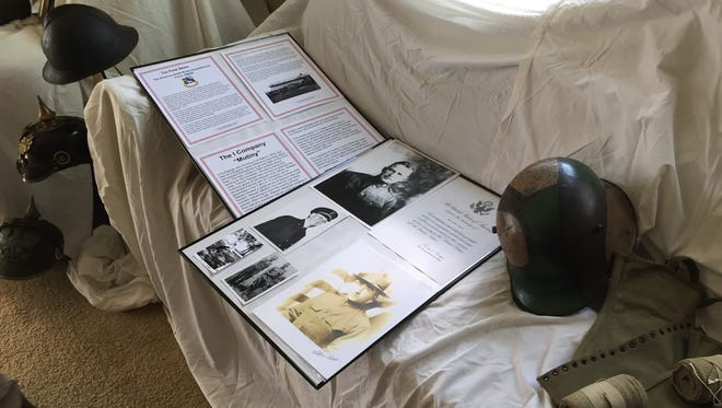 Documents, photos and helmets from World War I rest on a sofa at the Loop-Harrison Mansion.