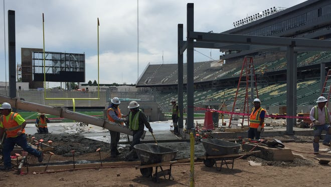 Workers pour concrete Wednesday for the New Belgium Porch in the north end zone of CSU's new on-campus stadium. The $220 million facility would cost at least $25 million more to build if construction began now rather than two years ago, the CSU system's chief financial officer said.