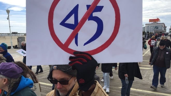 "A protester holds a sign Saturday, Feb. 17, with a line striking through the number 45, aka the 45th president Donald Trump. About 75 people gathered for a ""Not My President's Day"" march on the Boardwalk in Ocean City."