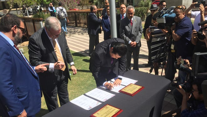 El Paso Mayor Dee Margo and Juárez Mayor Armando Cabada sign the sister cities agreement at San Jacinto Plaza in Downtown El Paso on Tuesday March 27, 2018.