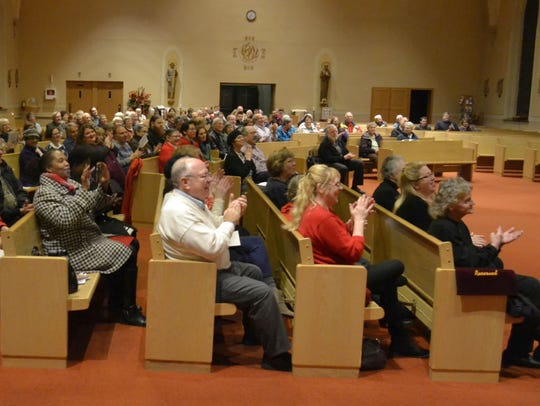 Attendees clap and give praise as the Rev. L.C. Green