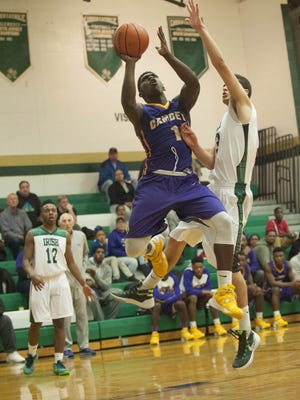 Camden's Brad Hawkins goes in for a layup past Dominic Dunn of Camden Catholic in  the third quarter of Wednesday's game.