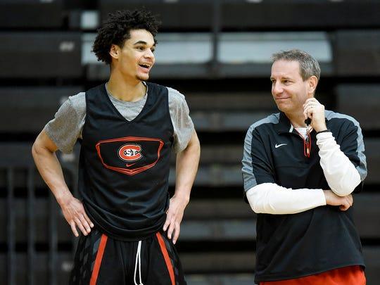 St. Cloud State's Gage Davis jokes with head coach Matt Reimer during practice Tuesday, Feb. 20, at Halenbeck Hall.