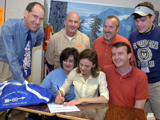Mike Foley, left, looks on in 2007 as a Mauldin High School athlete Brittanie SImmons signs a letter of intent to run cross country for Spartanburg Methodist College, where he was a coach.