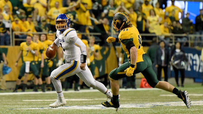 SDSU's Taryn Christion (3) runs away from NDSU's Caleb Butler (95) as he looks to pass during the NCAA Division I Football Quarterfinals at the Fargodome on Sat., Dec. 10, 2016.