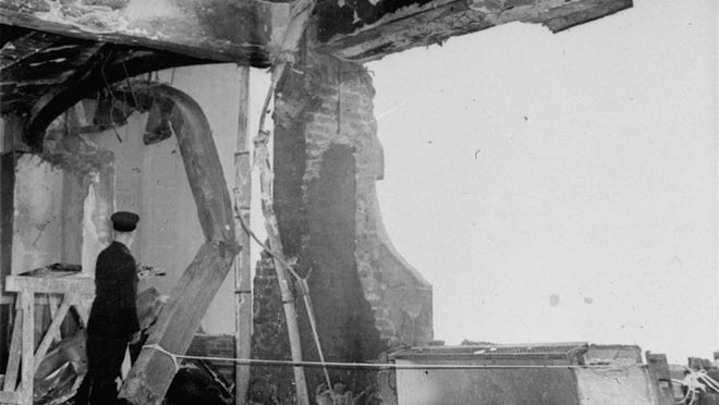 A fireman stands beside a twisted girder as he examines the gaping holes in the north side of the Empire State Building, on the 79th floor, evidence of the terrific impact with which a B-25 Army bomber crashed into the structure in New York on July 28, 1945.