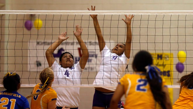 Kirtland Central's Jerica Holiday, left, and Iricia Thompson defend the net against Bloomfield on Thursday at Bronco Arena in Kirtland.