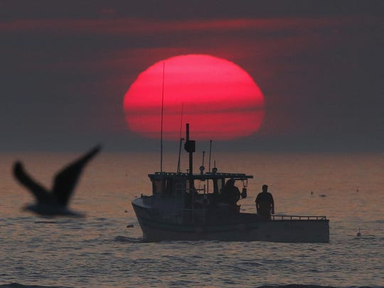 A lobster boat heads out to sea at sunrise Monday off Kennebunkport, Maine.