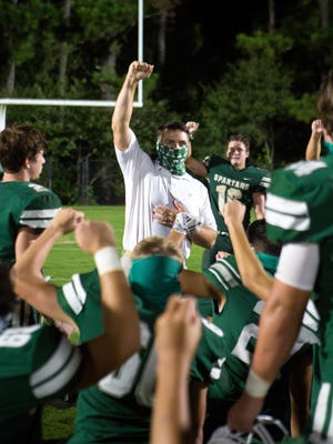 Athens Academy head coach Josh Alexander raises his fist with his players after the end of a varsity high school football game between the Athens Academy Spartans and the Commerce Tigers at Athens Academy in Athens, Ga., on Friday, Sept. 18, 2020. Athens Academy beat Commerce 24-7.