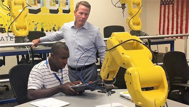 Ohio Secretary of State Jon Husted watches Asimiyu Raji, an employee at Honda, control a robot during a tour at RAMTEC on Wednesday.