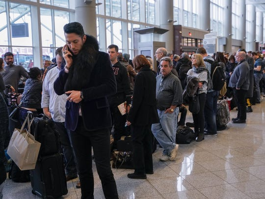 Passengers affected by a widespread power outage wait