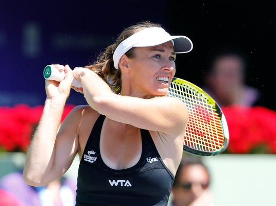 FILE - In this Wednesday, March 26, 2014, file photo, Martina Hingis, of Switzerland, returns the ball to Anabel Medina Garrigues, of Spain and Yaroslava Shvedova, of Kazakhstan, during her doubles match with Sabine Lisicki, of Germany, at the Sony Open Tennis tournament in Key Biscayne, Fla. Martina Hingis is returning to play at Wimbledon for the first time in seven years. The former singles and doubles champion from Switzerland was granted a wild card by the All England Club on Wednesday for the women's doubles tournament. Her partner is Russia's Vera Zvonareva, a former doubles winner and singles runner-up. (AP Photo/Joel Auerbach, File)