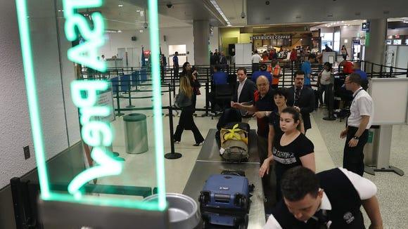 Travelers go through the TSA Pre-check line at Miami