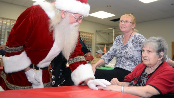 Santa talks with New Jersey Veterans Memorial Home resident Johanne Ressler and her visiting daughter Connie Reiter, of Mays Landing, during a gift giving event, Tuesday, Dec. 23 in Vineland.