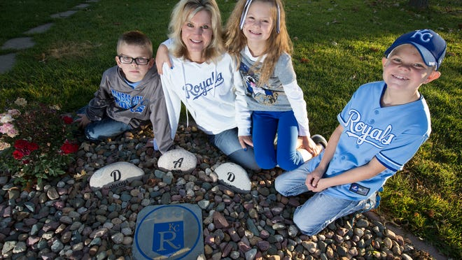 The Follmann family, Jack 8, Amy, Abby, 10, and her twin brother Ethan sit around a small memorial in honor of Brian. The rocks that spell out DAD are from classmates of the children and the Kansas City Royals rock was a gift from family friends. Brian Follmann was a devoted Royals fan from Massena who died in a farm accident in June at age 40.