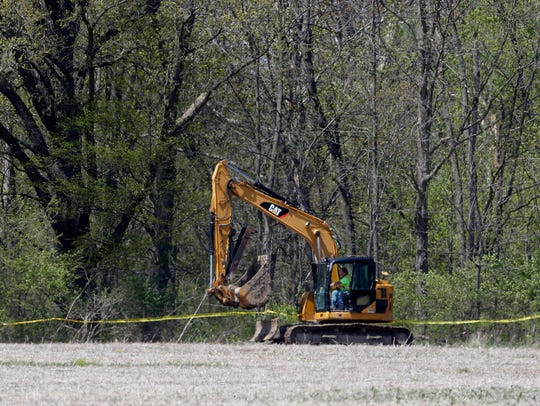 An excavator moves to a rural wooded area in Macomb