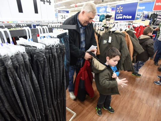 Volunteer Mike Lyons helped Jaxon Parks try on a coat