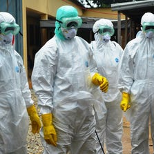 Guinea's Red Cross health workers wearing protective suits prepare to carry the body of a victim of Ebola.