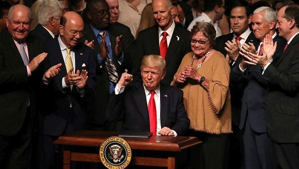 U.S. President Donald Trump gestures as he signs policy changes he is making toward Cuba at the Manuel Artime Theater in the Little Havana neighborhood on June 16, 2017 in Miami, Florida.