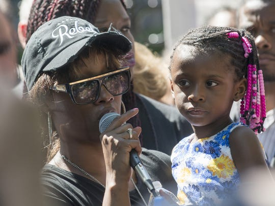 Diamond Reynolds, holding her daughter, speaks to a crowd outside the Governor's Mansion on July 7, 2016, in St. Paul, Minnesota.