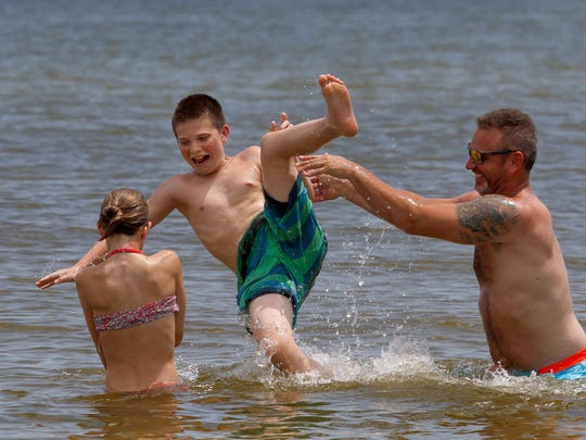 New Jersey resident Rob Simpson takes turns tossing Jack, 13, and Elle, 11, Friday at Sanibel Island's Lighthouse Beach.