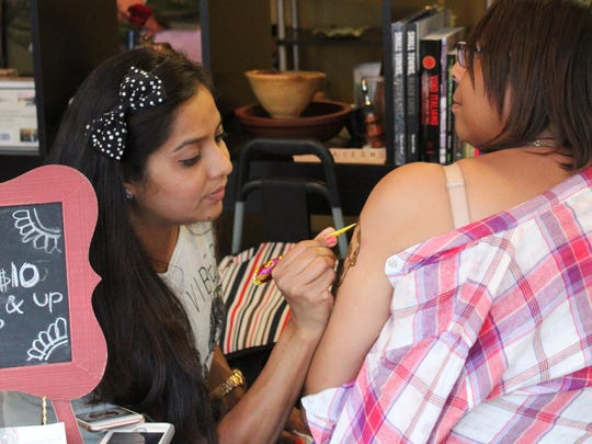 A visitor to the Noyes Museum receives a henna tattoo during Third Thursday.