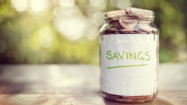 A glass jar full of coins, labeled savings and sitting on a wooden surface outdoors.