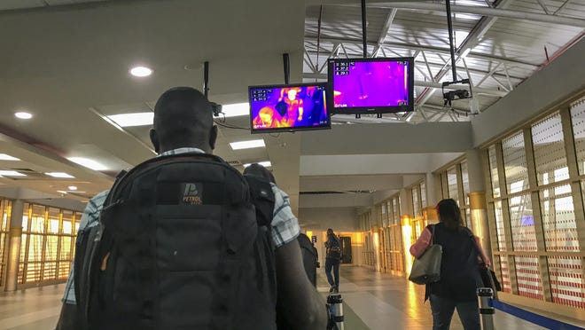 FILE - In this Thursday, Feb. 6, 2020 file photo, passengers from an Ethiopian Airlines flight from Addis Ababa walk past a thermal imaging camera checking for signs of fever as a screening mechanism against signs of infection from the new coronavirus or ebola, upon their arrival at the Jomo Kenyatta International Airport in Nairobi, Kenya. African nations face a difficult choice as infections are rapidly rising: Welcome the international flights that originally brought COVID-19 to the ill-prepared continent, or further hurt their economies.