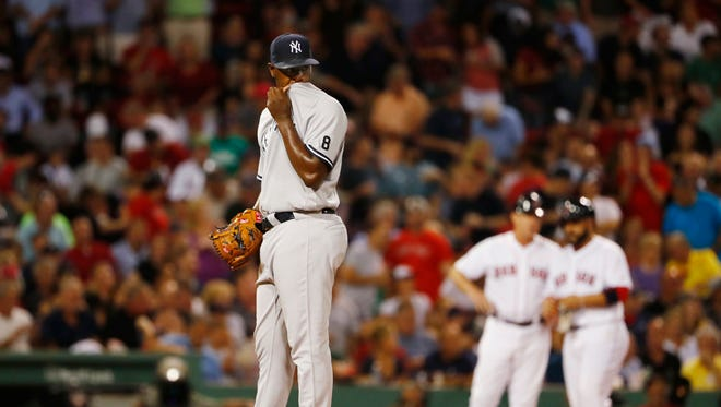 New York Yankees starting pitcher Luis Severino wipes his face after giving up a triple to Boston Red Sox's Sandy Leon, right, during the fifth inning of a baseball game at Fenway Park in Boston on Tuesday, Aug. 9, 2016.