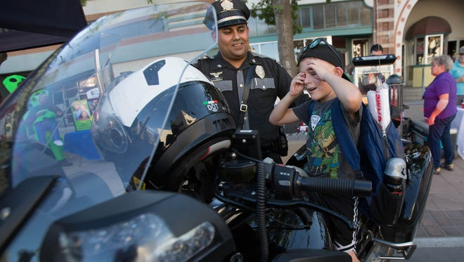 Officer Sonny Montez, left, with the New Mexico State Police, talks with Santos Zubia,6, who is sitting on a NMSP motorcycle during the National Night Out event, Monday August 7, 2018. Las Cruces Police and Fire Departments hosted a National Night Out. The event had booths from different state, local and national law enforcement agencies.
