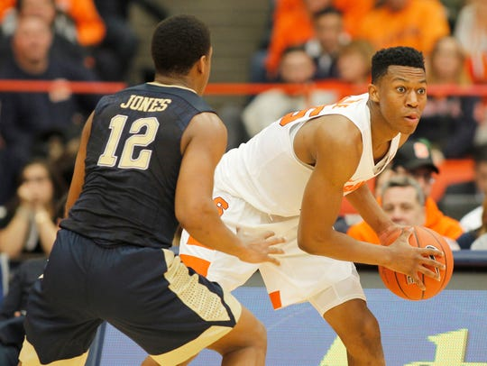 Syracuse's Tyus Battle, right, looks to pass the ball