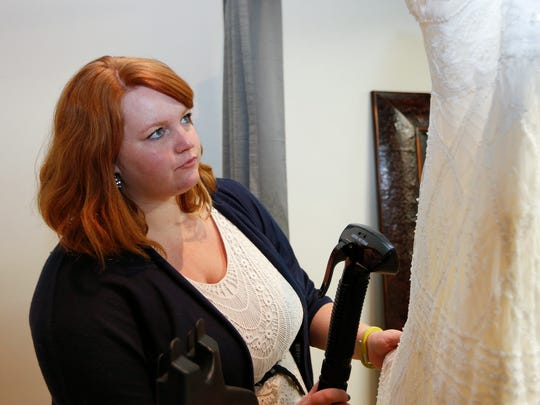Courteney Ferrin, owner of Belles and Lace Bridal, works in her Great Falls shop.