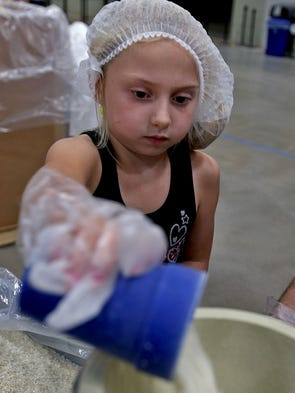 Heidi Beerbower, 7 of South Des Moines, added rice to other ingredients at Meals from the Heartland food packaging at Hy-Vee Hall in Des Moines on Friday afternoon August 29, 2014.
