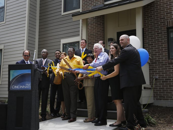 City Councilmen and those associated with the project perform a ceremonial ribbon cutting at the St. Ambrose Apartments, which is on the site of the now demolished St. Leger Apartments. In the crowd are Councilmen Charlie Winburn, Chris Smitherman, Wendell Young, Evanston Community Council President Anzora Adkins, and Vice Mayor David Mayor.