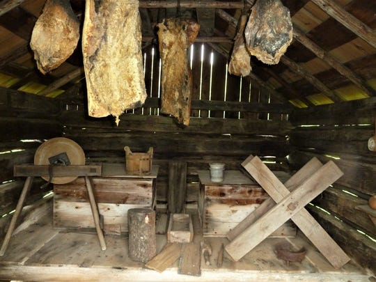 Hanging meat and tools dominate the plantation smokehouse interior.