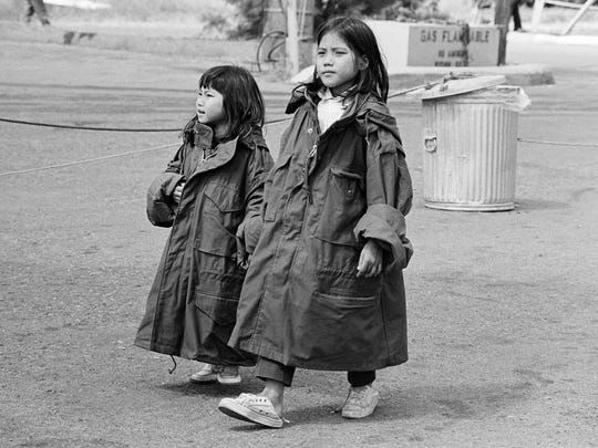 Two young Vietnamese refugees wear oversized GI issue