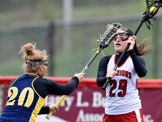 Susquehannock's Kayla Held, right, looks to pass the ball around Eastern's Haley Holtzinger during lacrosse action at Susquehannock High School in Shrewsbury Township, Tuesday, April 25, 2017. Susquehannock would win the game 23-8. Dawn J. Sagert photo