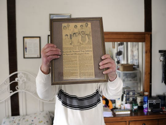 Gary Kiracofe shows off a framed article about his