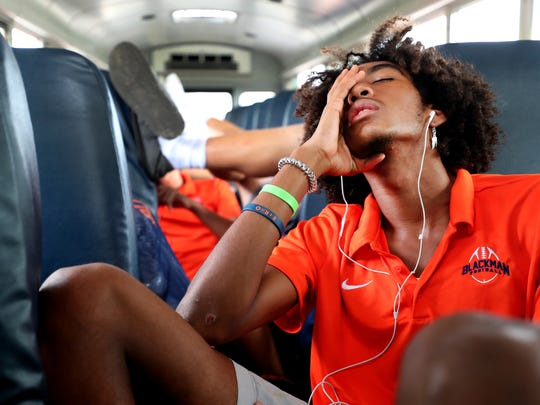 Blackman football player Emilio Martin rests while listening to headphones as the team travels to Florence, Ala.