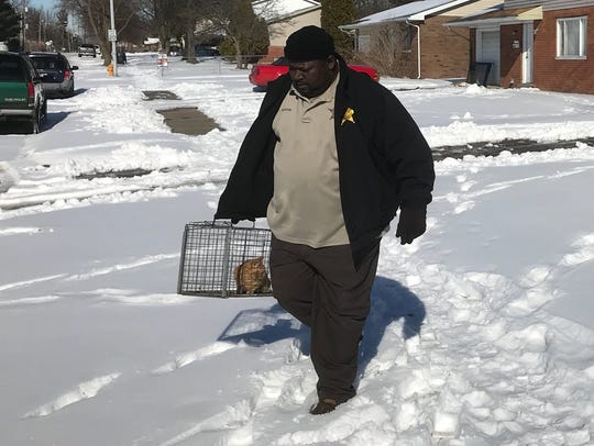 An animal control employee removes a cat from a home