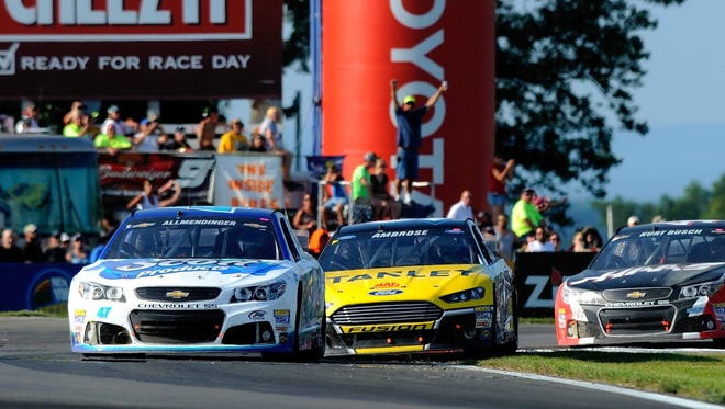 AJ Allmendinger, in the No. 47 Chevrolet, leads Marcos Ambrose, in the No. 9 Ford, during the Cheez-It 355 at The Glen last year.