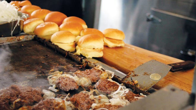 The White Manna Hamburgers restaurant in Hackensack was originally a booth at the Worlds Fair in Queens in 1939. It was moved from Queens to Hackensack in 1946. Some rumors say that White Castle was based on this burger joint. Here burgers cook on the grill.  Photo: Christopher Sadowski