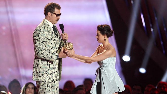This April 14, 2013, photo shows actress Aubrey Plaza, right, as she tries to take away an award presented to Will Ferrell during the MTV Movie Awards in Culver City, Calif.  Plaza approached the stage as Ferrell made his acceptance speech after winning the Comedic Genius award.
