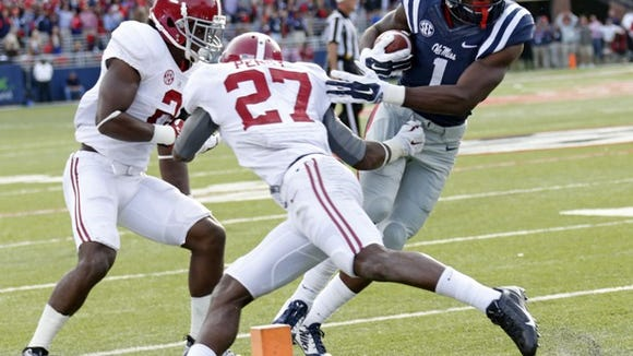 Mississippi wide receiver Laquon Treadwell (1) dodges Alabama defensive backs Nick Perry (27) and Tony Brown (2) for a 14-yard touchdown pass reception during the second quarter of an NCAA college football game in Oxford, Miss., Saturday, Oct. 4, 2014. (AP Photo/Rogelio V. Solis)